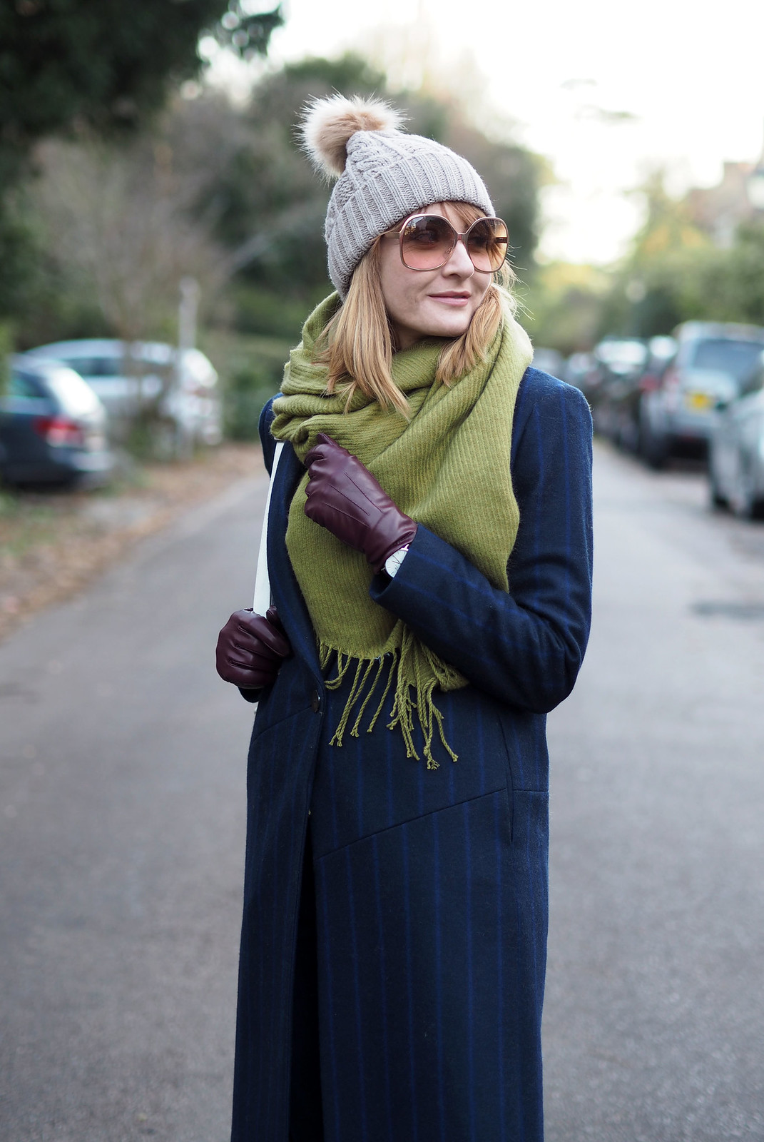 Smart cold weather layered outfit \ navy pinstripe wool coat \ moss green wool scarf \ bobble hat \ white backpack and Adidas Stan Smiths \ deep hem straight leg jeans | Not Dressed As Lamb, over 40 style