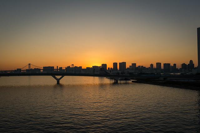 東京の高層ビル越しに沈む夕日の写真