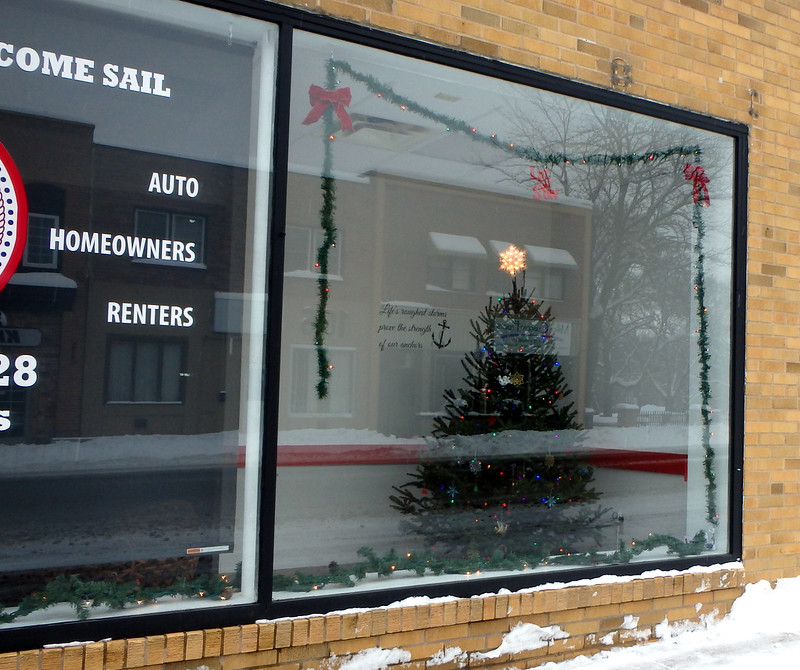 a Christmas tree in a storefront window, with garland bordering