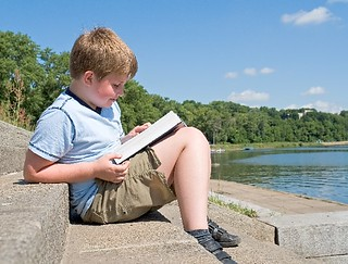 A little boy reads a big book with river at background | by MyTudut