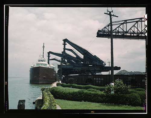 "Pennsylvania R.R. [Railroad] ore docks, unloading iron ore from a lake freighter by means of ""Hulett"" unloaders, Cleveland, Ohio  (LOC) 