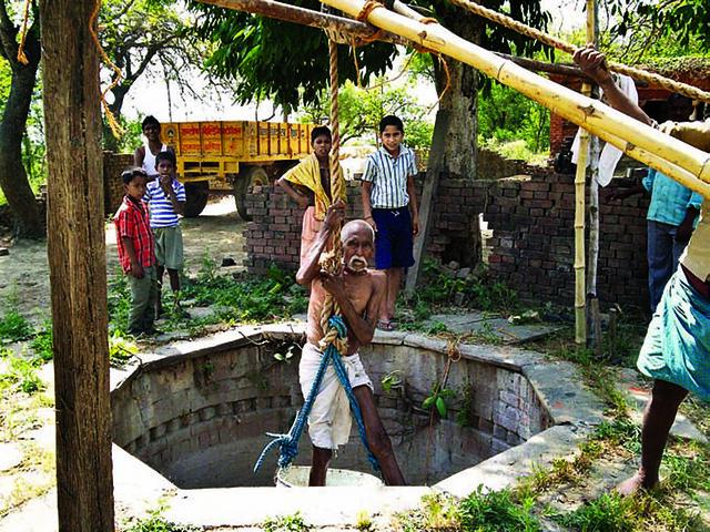आर्सेनिक प्रभावित क्षेत्र में कुएँ की सफाई करते ग्रामीण