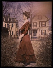 Woman wearing red dress with houses in background | by George Eastman House