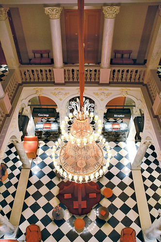 Lobby and hall, tiles in checkboard black and white with magnificent Chandelier at the Hotel de la Paix Geneva in Switzerland | by Concorde Hotels Resorts