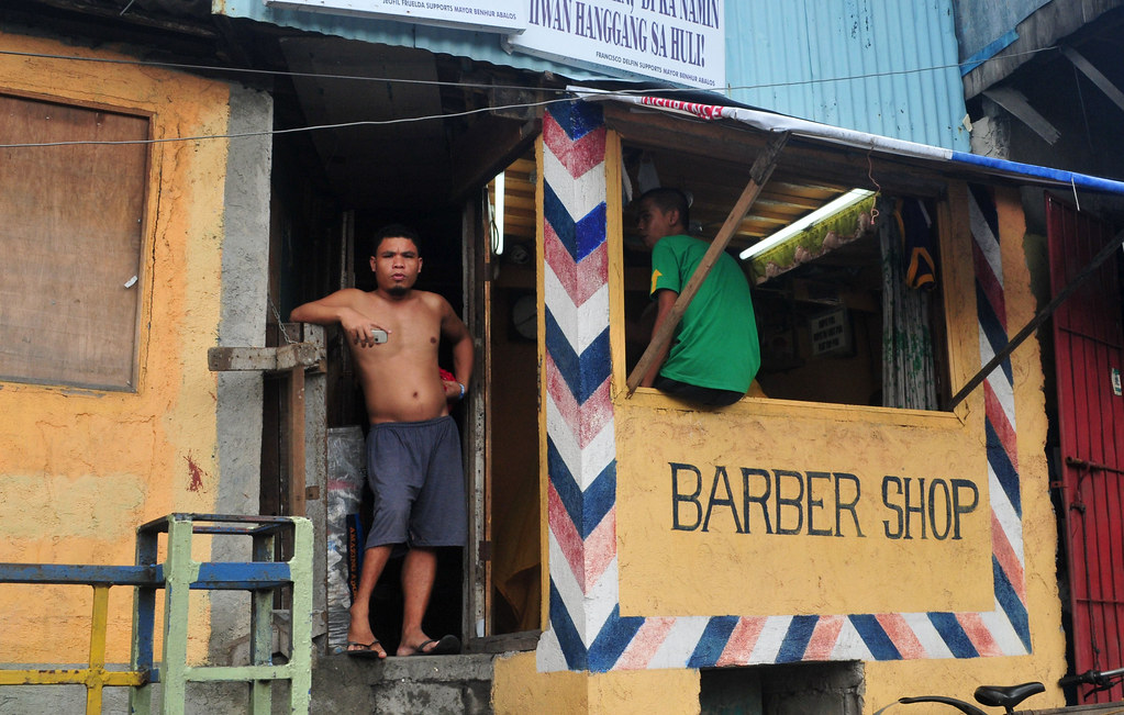 shirtless man standing by orange barber shop with handwritten sign