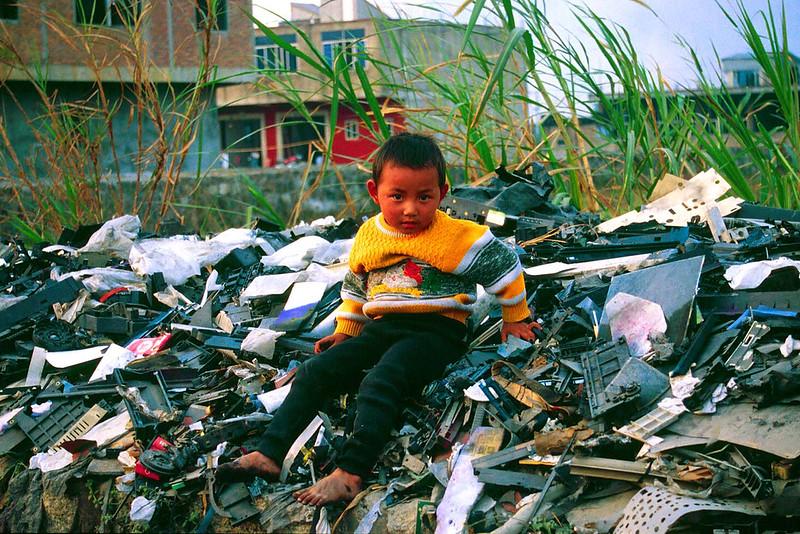Criança sentada numa pilha de lixo eletrônico na China. Foto:  Flickr/Basel Action Network (Creative Commons)