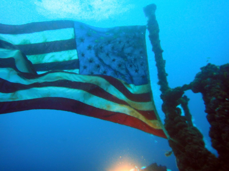 Underwater divers near the mast and flag on the USCGC Duane, Key Largo