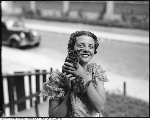 Billie Hallam, Miss Toronto 1937, posing with a kitten, in front yard of her home, 191 Booth Avenue | by Toronto History