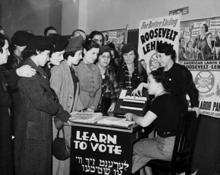 Women surrounded by posters in English and Yiddish supporting Franklin D. Roosevelt, Herbert H. Lehman, and the American Labor Party teach other women how to vote, 1935 | by Kheel Center, Cornell University Library