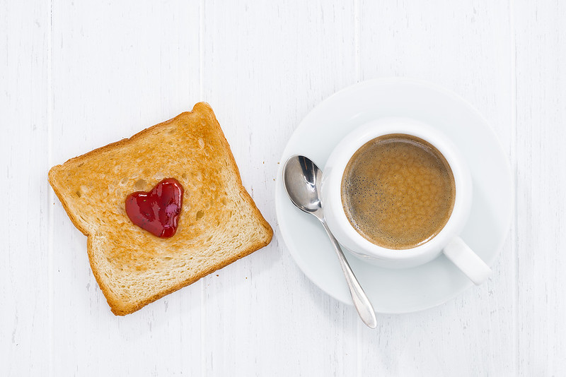 toast in heart shape with fruit jam and cup of coffee
