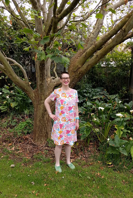 A woman poses in a garden in a retro floral print shift dress and green flock brogues.