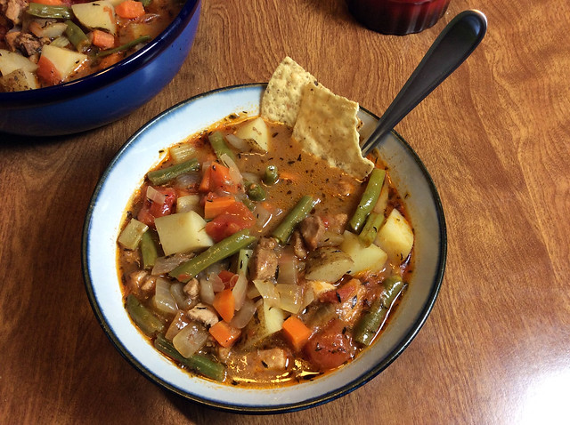 A bowl of chicken stew on a wooden table. Tucked into the edge of the bowl are a pair of tortilla chips, which is somewhat ridiculous from a logistical standpoint, since they'll just get mushy, but it looks nice.