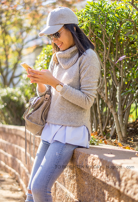 gray baseball cap, gray cowlneck sweater layered over baby blue peplum top, oversized watch, distressed lightwash skinny jeans, gray tote