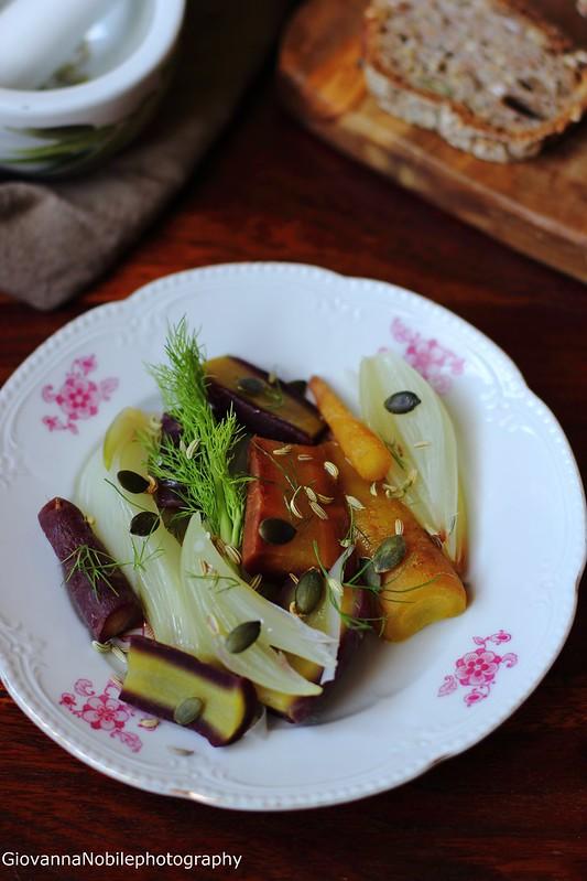 Ricette delle carote colorate, finocchi e cipolle al vapore, condite con citronette con le barbine del finocchio e semi di finocchio e zucca