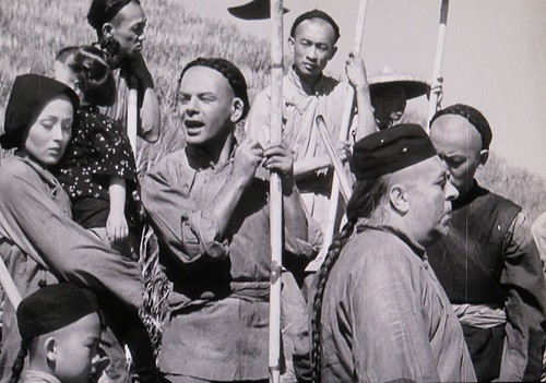 Richard Loo is visible standing behind Paul Muni in THE GOOD EARTH