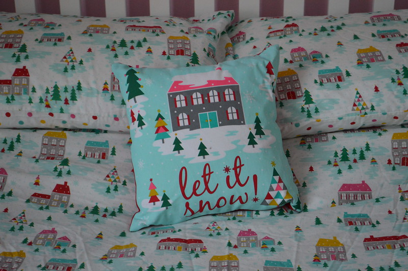This is a picture of festive bedding with christmas tress and snow