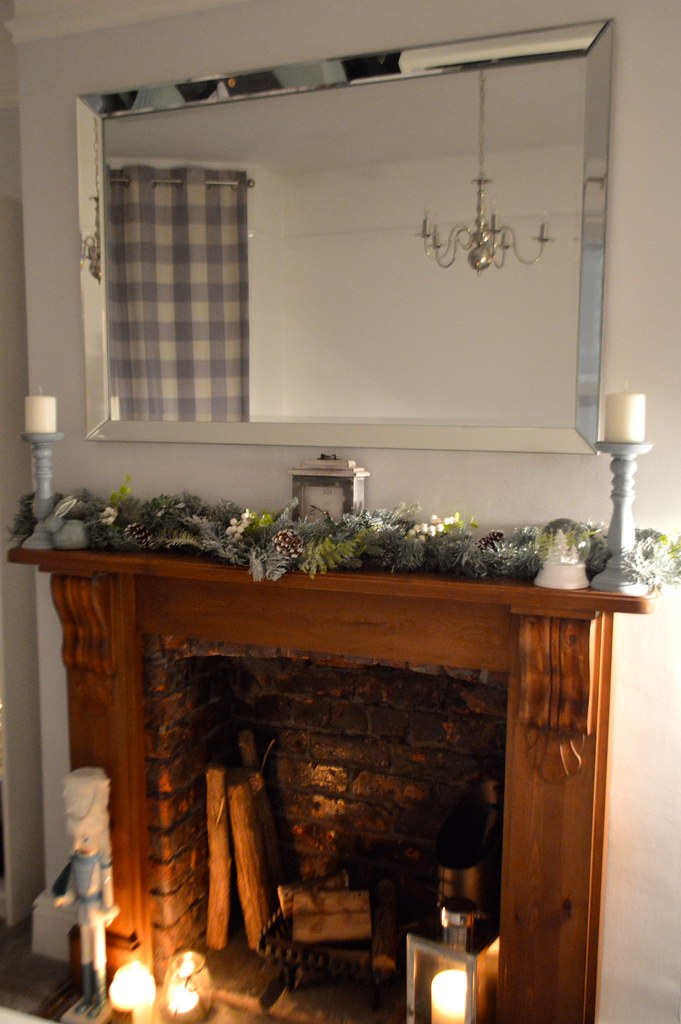 This is a picture of a festive fireplace with a snowy garland
