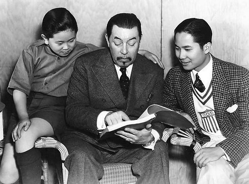 Warner Oland, in his Charlie Chan makeup, flanked by Layne Tom Jr. on the left and Keye Luke on the right