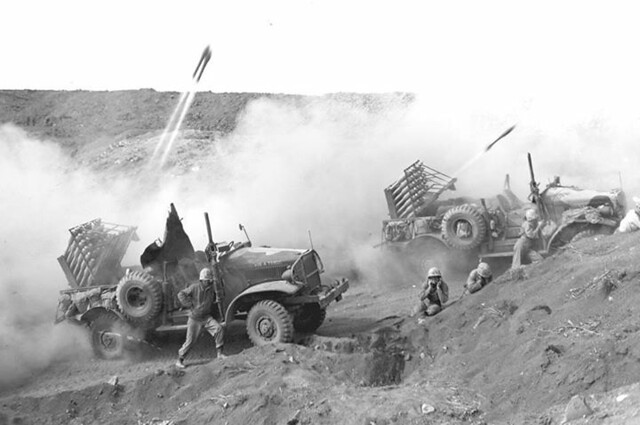 """Fireworks on Hell's Half Acre"" - The first rounds take flight as Marine rocketeers launch pyramids of projectiles toward Japanese emplacements in support of a Leatherneck advance on Iwo. February 28, 1945."