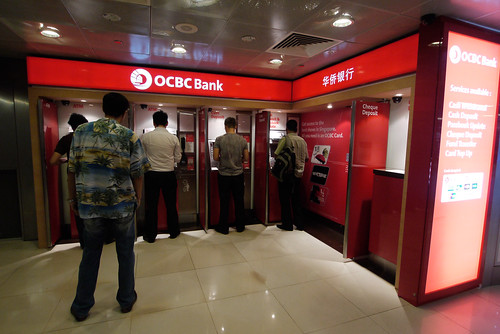 An OCBC ATM services customers at the Raffles Place MRT station on 12 August 2011. There are currently 6 local and 106 foreign banks operating in Singapore.