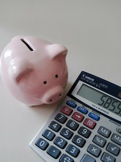 piggy bank beside calculator calculating investments