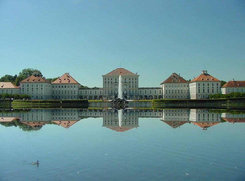 Nymphenburg Palace looking beautiful in the sun. The bright red roof is beautiful against the blue sky and the reflection is clear in the pond in the front