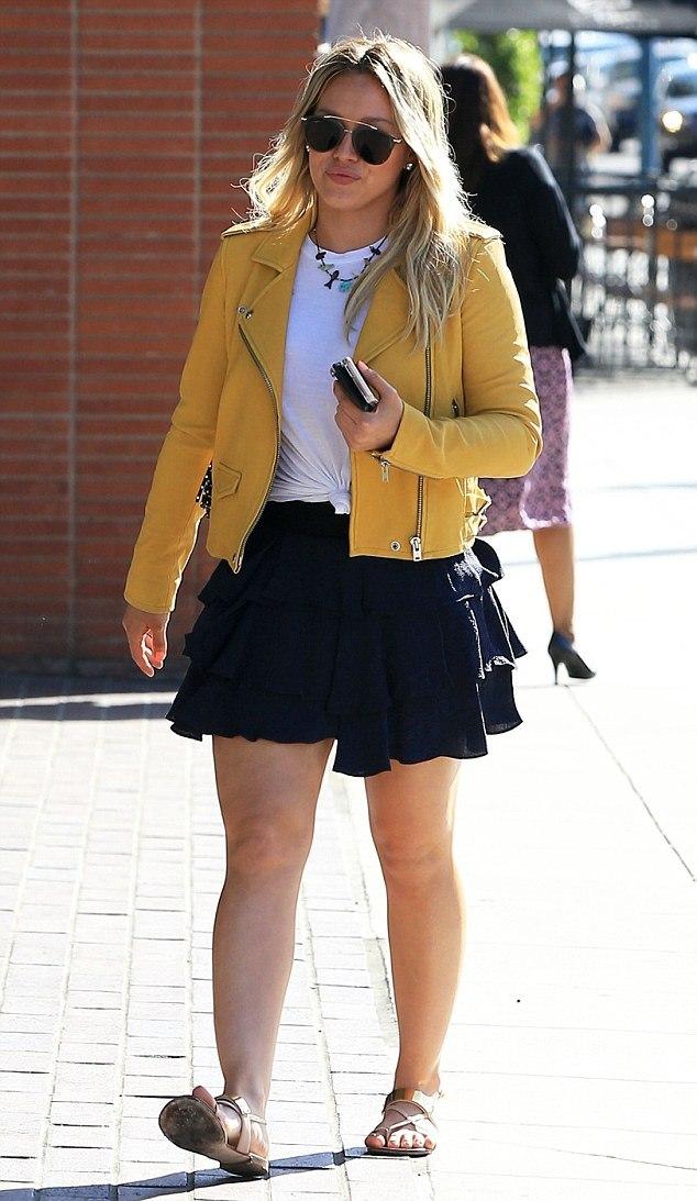 Hillary duff in a yellow biker jacket t-shirt black skater skirt and sandals