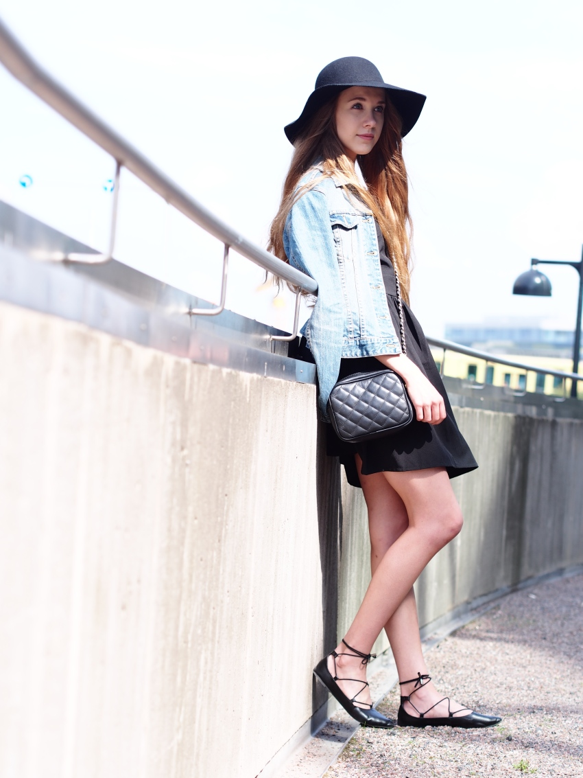 Little black dress in a causal way with denim jacket, a hat, lace up flats and cross body bag