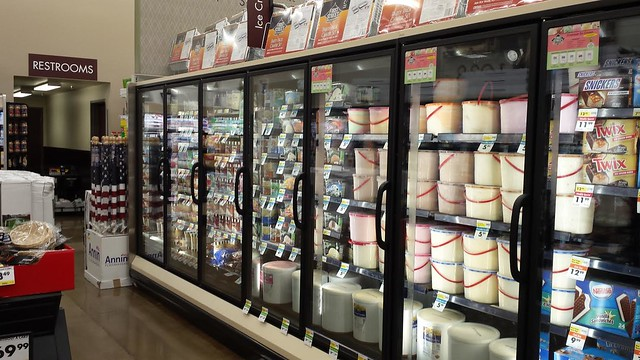 A grocery store isle with ice cream on the shelves.