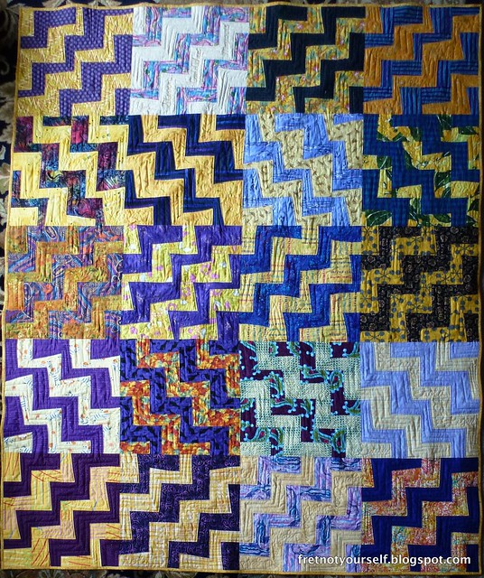 Free-hand cut strips of purple and gold create a rail fence variation in this quilt.