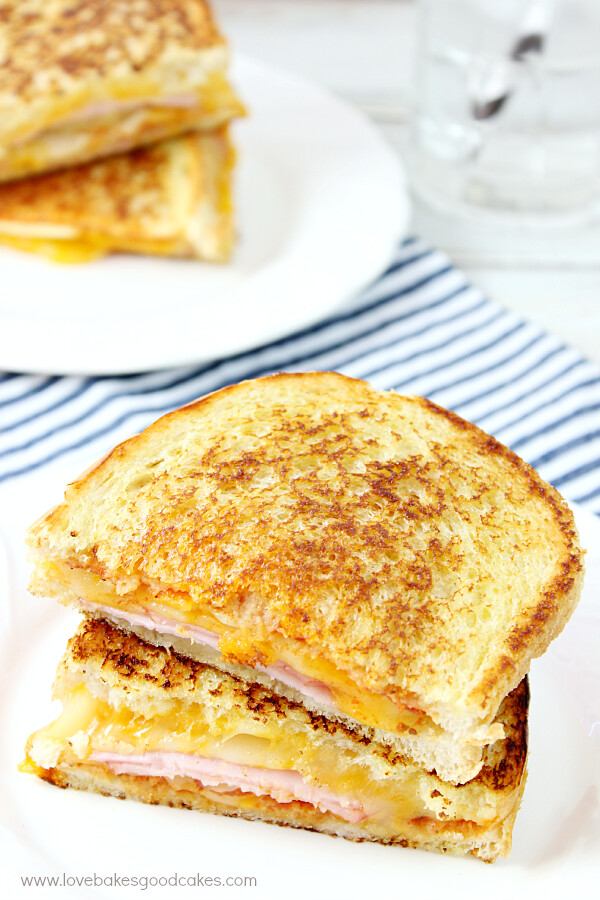 Hawaiian Pizza Grilled Cheese Sandwich cut in half and stacked on a plate.