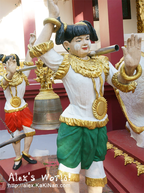 Statues outside the temple hoisting a bell