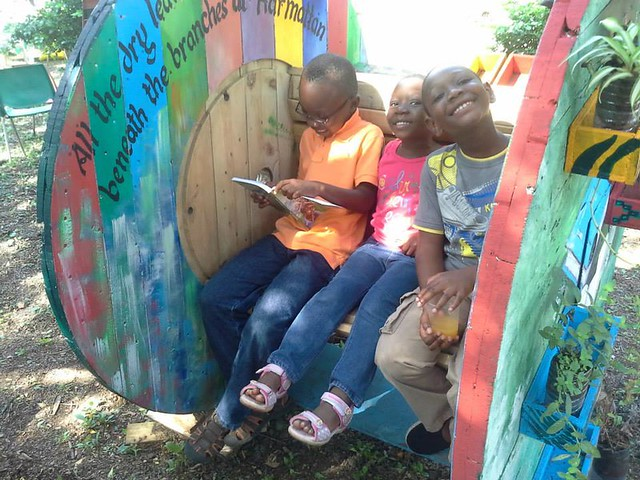 Children reading on a repurposed cable spool at Mmofra Place.