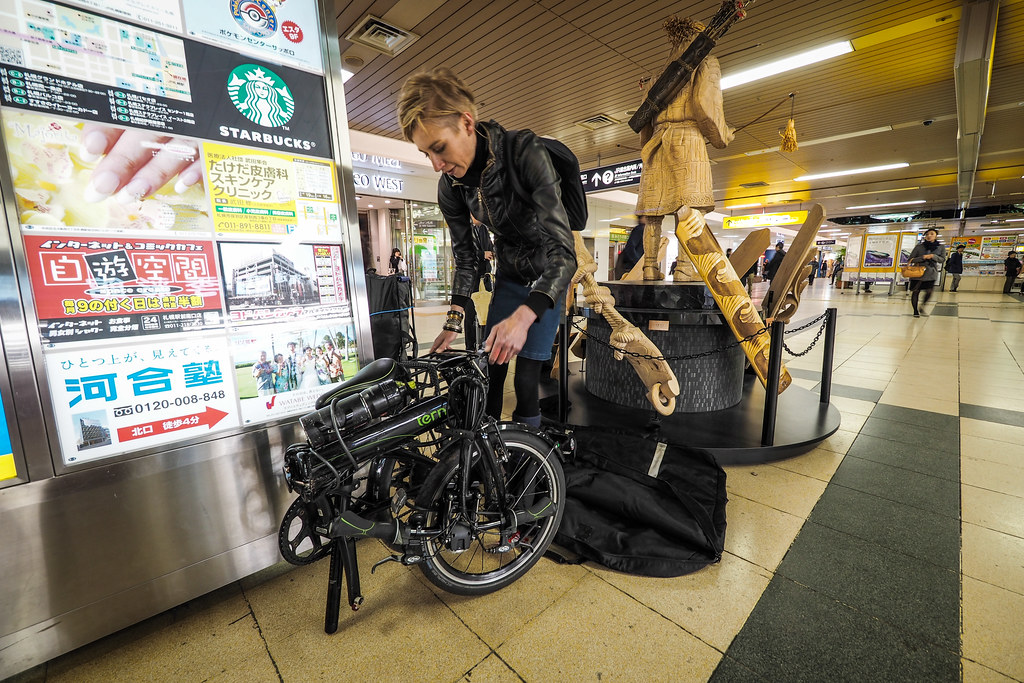 Packing up a Tern folding bicycle for train travel in Sapporo station, Japan