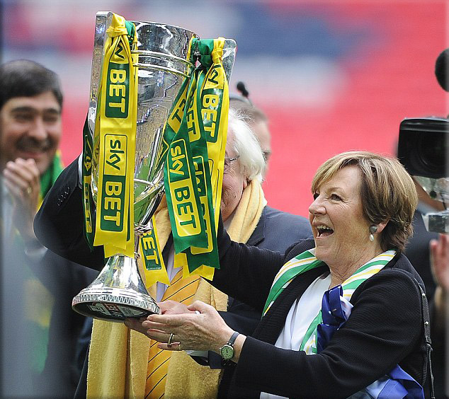 Norwich owner Delia Smith holds the play-off trophy up to the fans