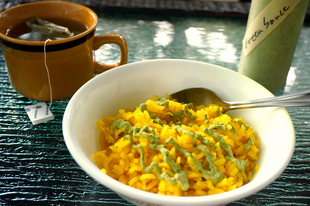 A bowl of yellow rice sit sin the foreground, drizzled with pale green cilantro sauce. A squeeze bottle labeled 'green sauce' is in the background, as is a mug of tea. You can tell from the tea that this photo is staged, because I need a far more caffeinated beverage in the morning.