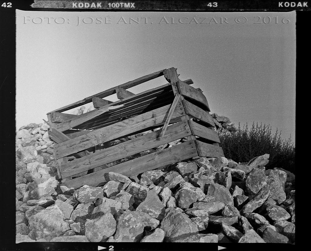 fotografía química en blanco y negro de un gran cajón de madera sobre un montón de piedras.