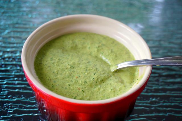 Closeup shot of pale-green cilantro sauce in a bright red ramekin