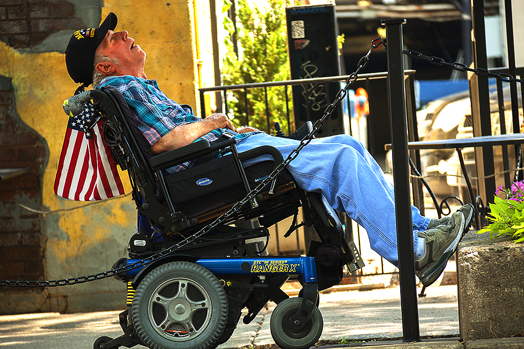 Vietnam veteran on motorized wheelchair with flag--Ann Arbor