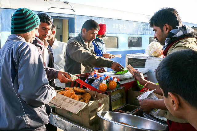 Passengers buying foods at a station on the way to Jaisalmer, India ジャイサルメール行きの列車の途中駅で食べ物を買う人々