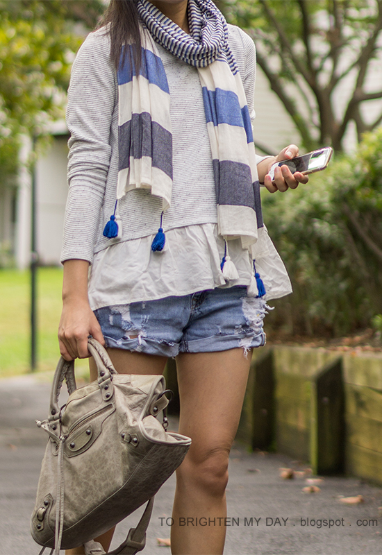 blue and gray striped scarf with tassels, gray ruffled sweatshirt, distressed shorts, gray moto bag