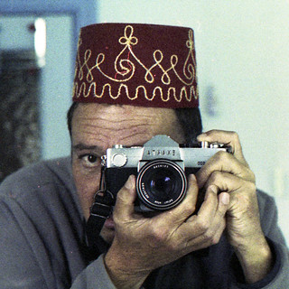 reflected self-portrait with Exakta TL500 camera and decorated Fez (square crop)