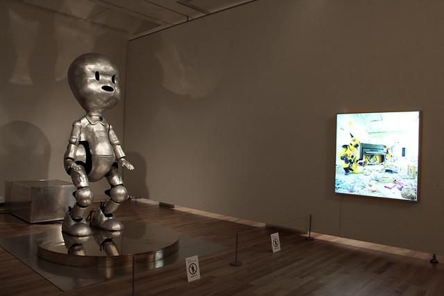 右《アトムスーツ・プロジェクト:保育園4・チェルノブイリ》(1997/2003)。チェルノブイリの廃墟となった幼稚園にあった人形を、《アトムスーツ》を着たヤノベケンジが拾い上げる写真。壁面には太陽が描かれている。 左《ビバ・リバ・プロジェクト-スタンダ-》。上記作品から着想。初期設定では一定量の放射線を検知すると、うつぶせ状態から立ち上がる。人形に命が吹き込まれて再生することをコンセプトにしている。また、第一子が誕生してつかまり立ちの時期と重なっていることと、ヤノベケンジ自身もチェルノブイリの体験を、前向きに昇華するために、魂の再生という意味も作品に込めている。