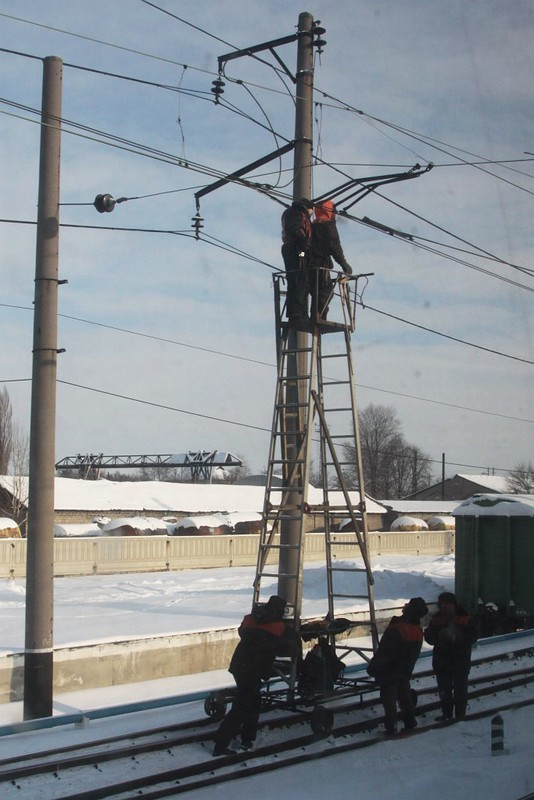 Railway staff inspect the overhead wires