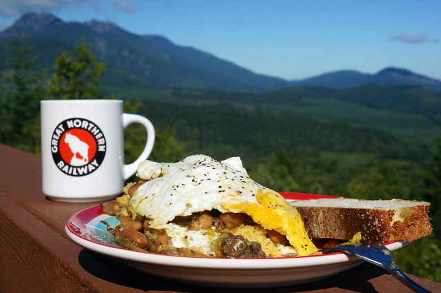 "A plate of beans and cornbread (and a mug of coffee reading ""Great Northern Railway"" sits on a porch rail in the bright sunshine, with Mt. Angeles rising in blues and greens in the background."