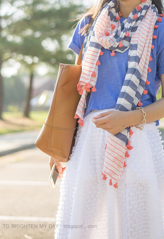 striped and pom pom scarf, cornflower blue tee, pave link bracelet, white clip dot midi skirt, cognac brown tote