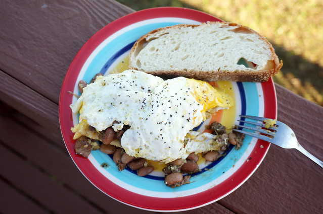 Overhead shot of a plate of beans and cornbread, the main event almost entirely obscured by a fried egg, heavily peppered.