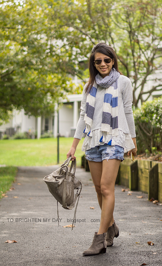 blue and gray striped scarf with tassels, gray ruffled sweatshirt, distressed shorts, gray moto bag, taupe suede ankle boots